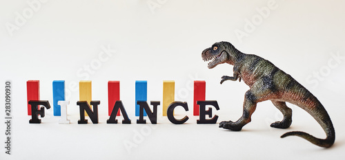 Finance word created with alphabet letters. Dinosaur toy standing near multi-colored wooden blocks in the background