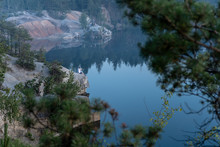 Dramatic Scenic View Of The Granite Quarry Filled With Blue Water, And The Photographer On The Rock, After Sunset At Dusk In The Summer. Treaveling As Lifestyle. Picturesque Landscape