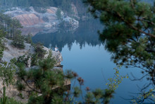 Dramatic Scenic View Through The Trees Of The Granite Quarry Filled With Blue Water, And The Photographer On The Rock, After Sunset At Dusk In Summer. Treaveling As Lifestyle. Picturesque Landscape