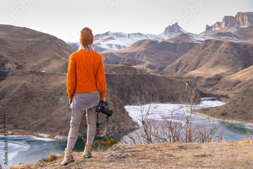 Foto auf AluDibond Lachs Portrait from the back of the girl traveler photographer in an orange sweater and hat with a camera in hand in the mountains against the background of a frozen mountain lake. Photo travel concept