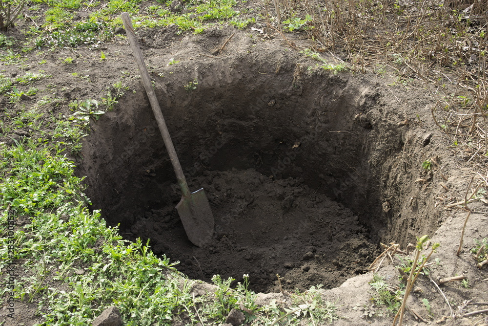Fototapeta Deep pit in the ground. In the pit lies a shovel. Digging a hole.