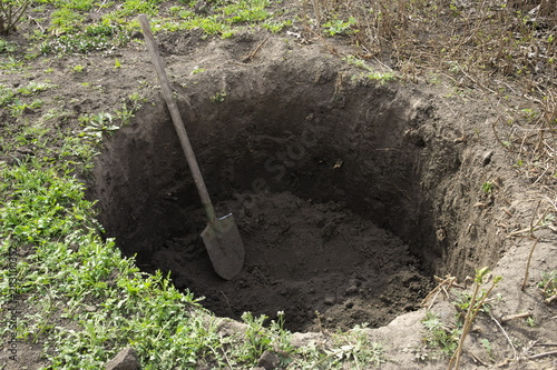 Fotografie, Obraz Deep pit in the ground. In the pit lies a shovel. Digging a hole.
