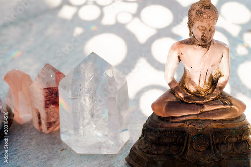 Transluscent pink Buddha statue with healing Reike crystals. Wallpaper Mural
