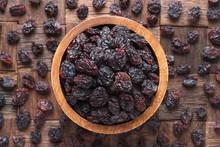 Dried Grapes, Dark Raisins In Wooden Bowl, Top View.