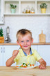canvas print picture - Happy little boy eating mixed vegetables salad