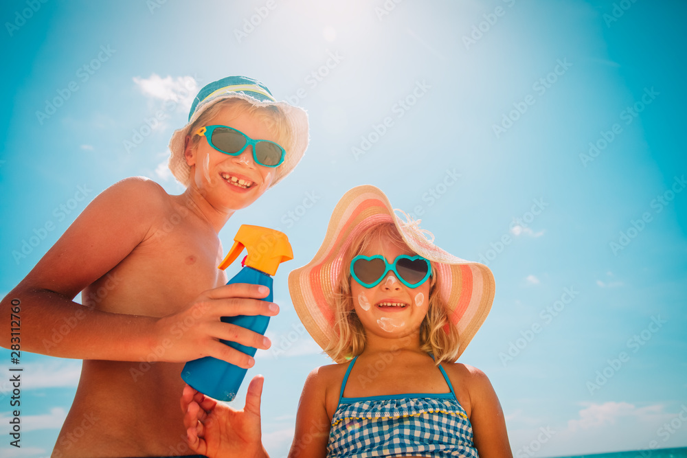 Fototapety, obrazy: sun protection, cute girl and boy with sun cream at beach