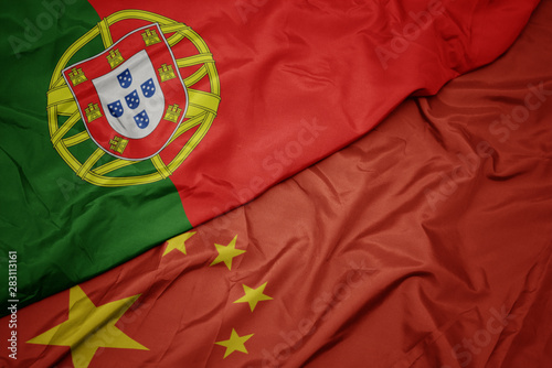 Photo  waving colorful flag of china and national flag of portugal.