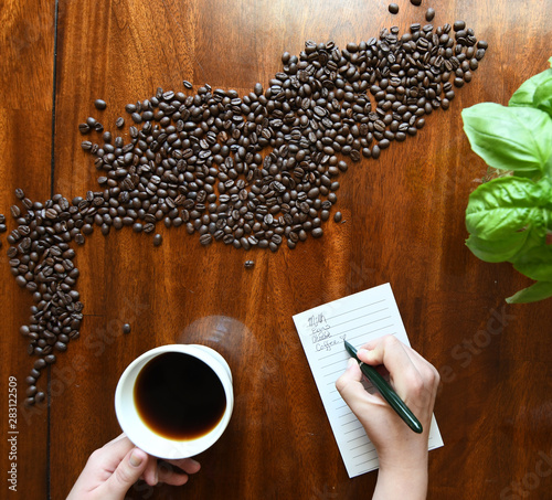 Fényképezés Woman's hands writing down a grocery list while having coffee