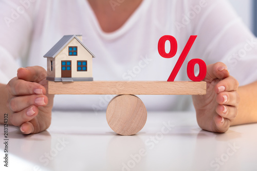 Photo  Balancing Of Red Percentage Sign And House Model On Seesaw