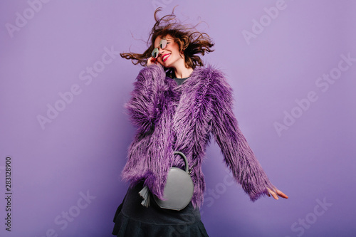 Laughing curly woman in sparkle sunglasses dancing on purple background. Happy girl in fluffy coat enjoying photoshoot in winter clothes.