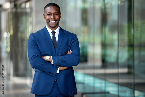 Valokuvatapetti Smiling african american businessman CEO standing proud with arms crossed outsid