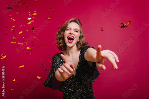 Valokuvatapetti Inspired short-haired fun lady dancing under sparkle confetti and laughing