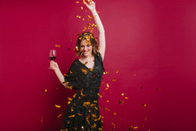 Joyful Attractive Female Model Dancing With Pleasure And Throwing Out Golden Confetti. Adorable Caucasian Girl In Black Clothes Having Fun At Festive And Tasting Red Wine.