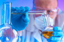 In The Chemical Laboratory Experience Is Put. The Scientist Mixes Chemical Liquids From A Test Tube And From A Flask. The Chemist Holds A Flask With A Yellow Substance. Scientific Research. Scientist