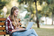 selective focus of beautiful girl in casual clothes sitting on wooden bench in park and using laptop