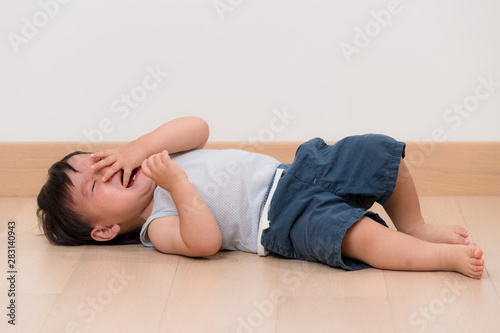 Fotografering Asian little boy cry and lying on floor
