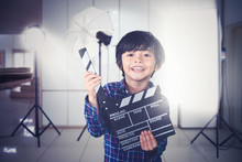 Little Boy Holds Clapperboard During Film Production