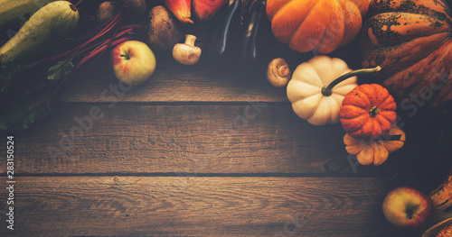 Fototapeta Frame of fall healthy vegetarians food. Cooking background. Ingredients for Thanksgiving day dinner. Corn, pumpkin, fruits over wooden table, top view. obraz