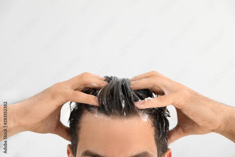 Fototapeta Man applying shampoo onto his hair against light background, closeup. Space for text
