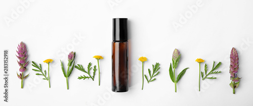 Fotografie, Tablou  Bottle of essential oil and wildflowers on white background, top view