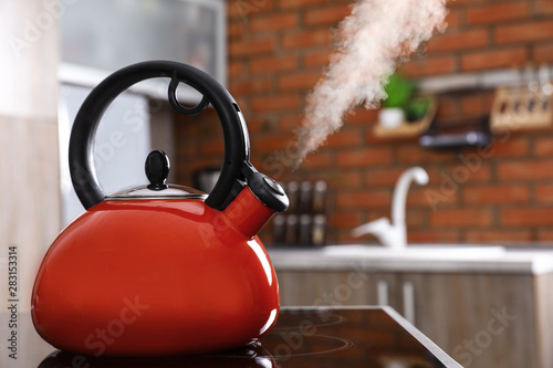 Modern kettle with whistle on stove in kitchen, space for text Slika na platnu