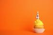 Leinwandbild Motiv Birthday cupcake with number four candle on orange background, space for text