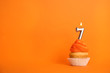 canvas print picture - Birthday cupcake with number seven candle on orange background, space for text