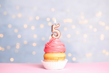 Birthday Cupcake With Number Five Candle On Table Against Festive Lights