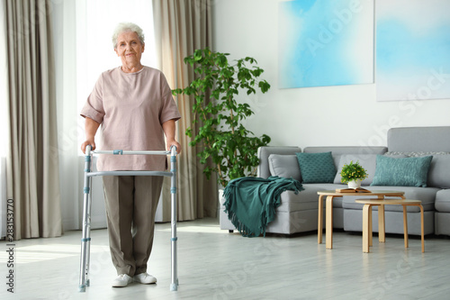 Photo Elderly woman using walking frame indoors. Space for text
