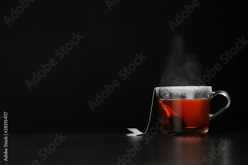 Poster Ouest sauvage Glass cup of hot tea on table against black background, space for text