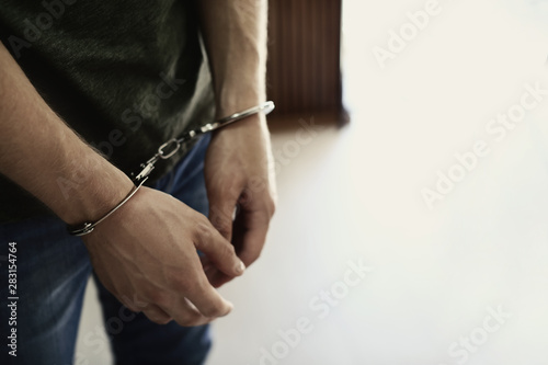 Man detained in handcuffs indoors, space for text. Criminal law Wallpaper Mural