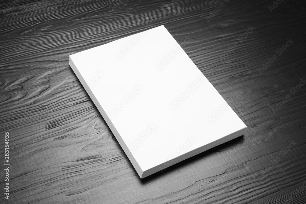 Fototapeta Stack of blank paper sheets for brochure on black wooden background. Mock up