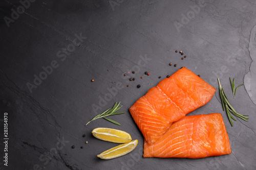 Obraz na plátně  Tasty salmon fillet on black slate surface, flat lay