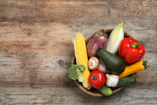 Wicker Bowl With Different Fresh Vegetables On Wooden Background, Top View. Space For Text