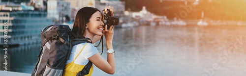 Fototapeta side view of asian woman with backpack taking photo obraz