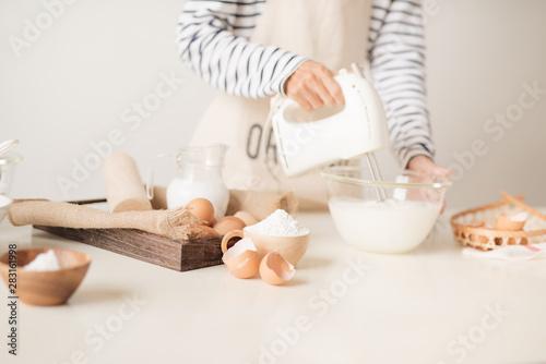 Fotografia Mixing white egg cream in bowl with motor mixer, baking cake