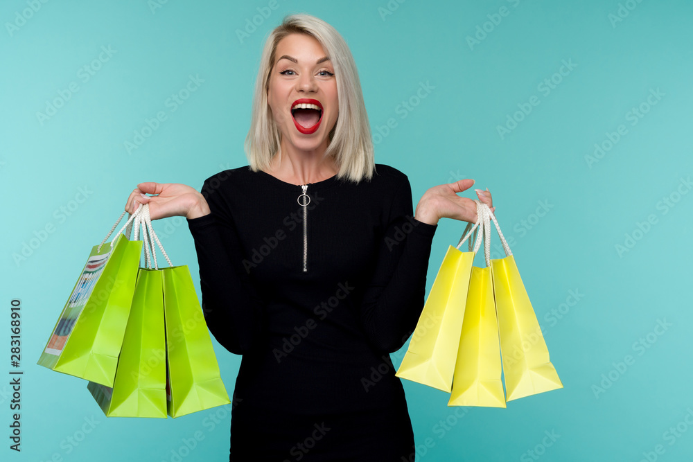 Fototapeta Young smiling woman holding shopping bags in black friday holiday. Happy Girl on blue background