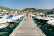 Back View Tourist Woman Woman Walking By Dock Boats On Background. Summer Time, Vacation In Spain, Malorca. Puerto De Soller Port Of Mallorca With Lllaut Boats In Balearic Island