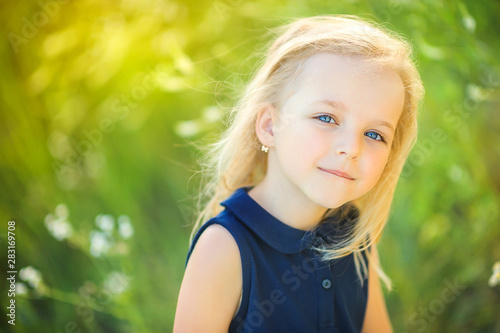 Obraz lovely cute little girl playing outdoors at sunset, walking on the field, happy childhood - fototapety do salonu