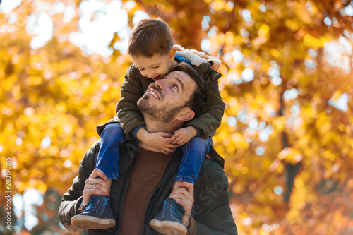 Happy father and little son playing and having fun outdoors over autumn park bac Billede på lærred