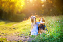 Little Girl Hugs A Beagle Puppy, Sitting On The Grass In The Park And Watching The Sunset, Best Friend
