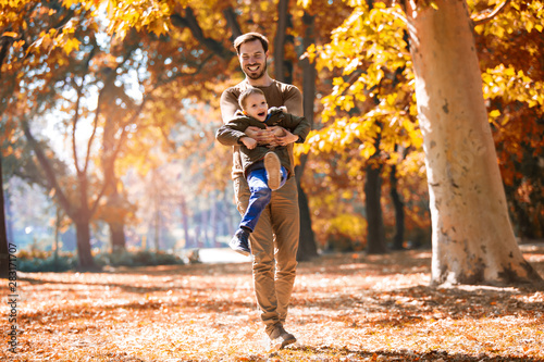 Pinturas sobre lienzo  Happy father and little son playing and having fun outdoors over autumn park bac