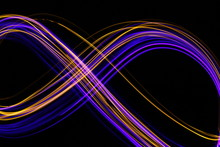 Long Exposure, Light Painting Photography.  Vibrant Abstract Streaks Of Neon Pink And Gold Color Against A Black Background.