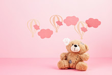 Cute Teddy Bear Over The Pink Pastel Background With Clouds And Ballons