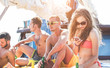 Happy friends doing boat party in caribbean sea - Young people having fun drinking beer and traveling in tropical sea tour - Summer holiday and vacation concept - Focus on right girl face