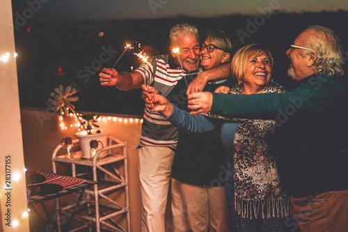 Fotomural  Group of senior friends celebrating birthday with sparkler fireworks on patio te