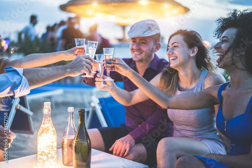 Photo Happy friends cheering and drinking champagne at beach party outdoor - Young peo