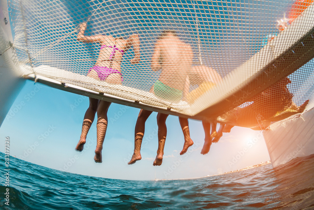 Fototapety, obrazy: Young friends chilling in catamaran boat - Group of people making tour ocean trip - Travel, summer, friendship, tropical concept - Focus on guys legs - Water on camera - Fisheye lens distortion