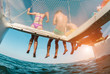 canvas print picture - Young friends chilling in catamaran boat - Group of people making tour ocean trip - Travel, summer, friendship, tropical concept - Focus on guys legs - Water on camera - Fisheye lens distortion