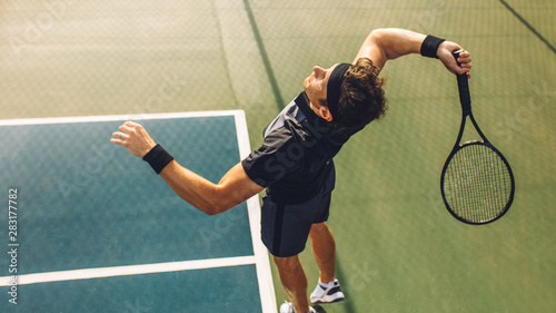 Tennis player serving in the match Fototapet